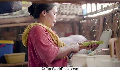 Asian woman cutting vegetable while cooking food on home...