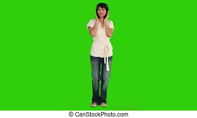 Asian woman dancing while she is listening to music -...