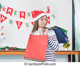 Asian woman disappointed about payment when buy a lot of christmas gift in shopping bags, upset expenses after shopping time, unhappy girl poor shopaholic, overspending, spent all money in holiday