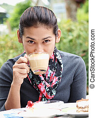Asian woman drinking a coffee