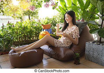 Asian woman drinking a cup of coffee and enjoy nature view
