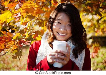 Asian woman drinking a warm drink