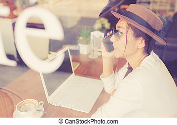 Asian woman drinking coffee and using computer in cafe.