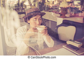 Asian woman drinking coffee and using computer in cafe, take pho