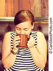 Asian woman drinking coffee in cafe. (Vintage process tone)