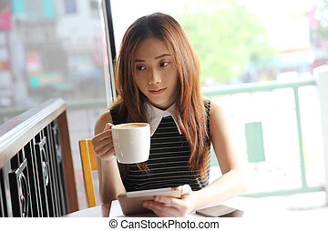 Asian woman drinking coffee with tablet