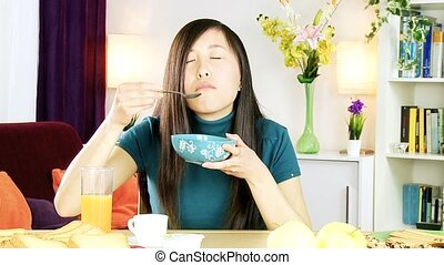 Asian woman eating cereals