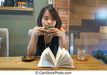 Asian woman enjoy free time with book, coffee and music