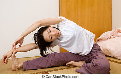 Asian woman excise on ground of room in home.