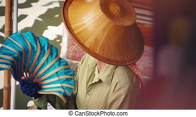 Asian Woman Fans Herself On Boat