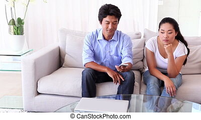 Asian woman fed up as boyfriend ignores her at home in...