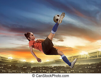 Asian woman football player kick ball