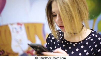 Asian woman girl typing text on a smartphone that is in a black silicone case in the shape of a cat