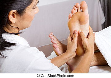 professional foot massage - asian woman giving professional...