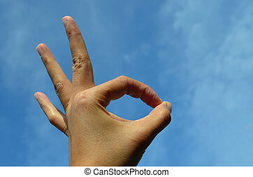Asian woman hand showing ok sign or peace against blue sky