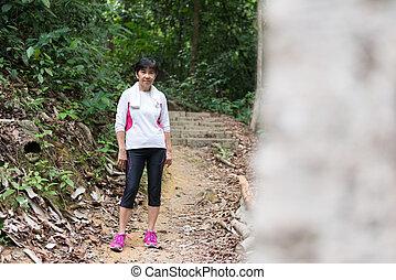 Asian woman hiking in jungle