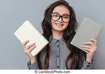 Asian woman holding books in hands