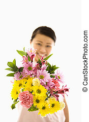 Asian woman holding flowers.