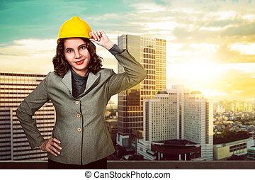 Asian woman holding hard hat