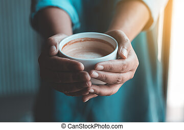 Asian woman holding hot coffee