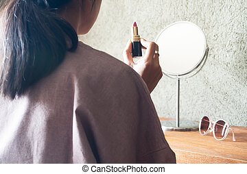 Asian woman holding lipstick preparing makeup to go out. Beauty and lifestyle concept