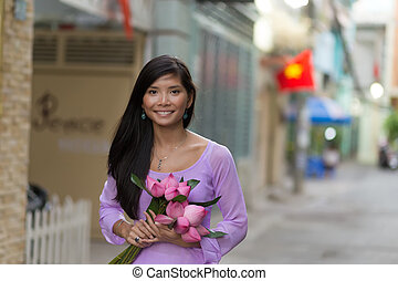 Asian woman holding lotus flowers