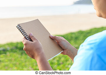 Asian woman holding notebook on the beach