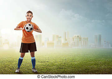 Asian woman holding soccer ball