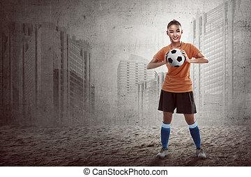 Asian woman holding soccer ball
