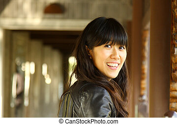 Asian woman in a garden smiling