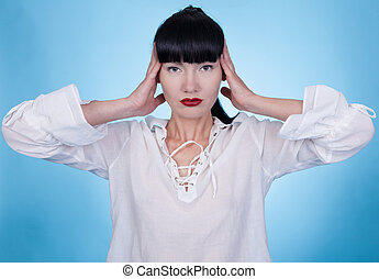 Asian woman in a white shirt posing with her hands on her head