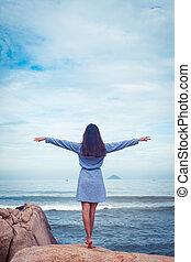 Asian woman in dress back stand, hands to the sides on a stone by the sea