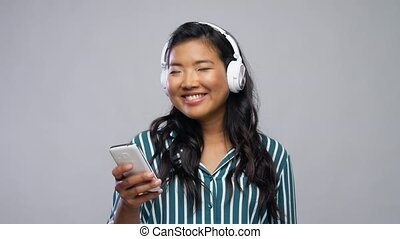 asian woman in headphones listening to music - people, ...