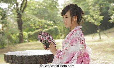Asian woman in Japanese garden wavi - Asian woman in kimono...