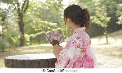 Asian woman in kimono waving a fan