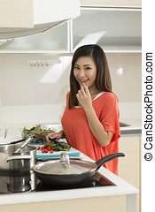Asian woman in kitchen preparing food