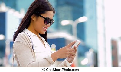 asian woman in sunglasses using smartphone in city -...