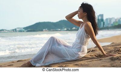Asian woman in white dress sitting on the beach near sea. Sun, sand and waves.