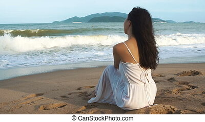 Asian woman in white dress sitting on the sand near sea. Sun, sand and waves.