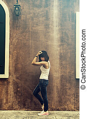 Asian woman in white vest and jeans look like a healthy woman posing by the wall