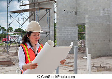 Asian Woman Inspector on construction site. Scaffolding,...