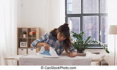 asian woman ironing bed linen at home