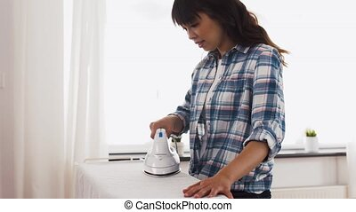 asian woman ironing bed linen at home - housework, laundry...