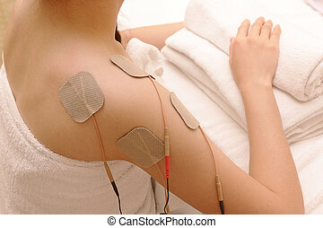 Asian woman is doing massage of electrical -stimulation ( TENs ) for the shoulder