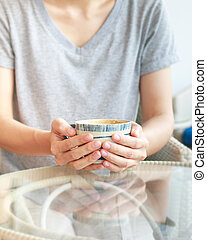 Asian woman is holding a cup of hot coffee on glass table. Focused at hand.