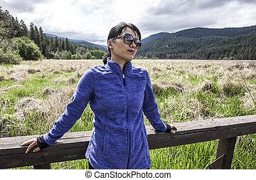Asian woman leans against railing.