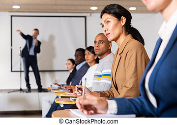 Asian woman listening to speaker at business training