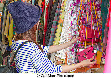 Asian woman looking at bags on rack