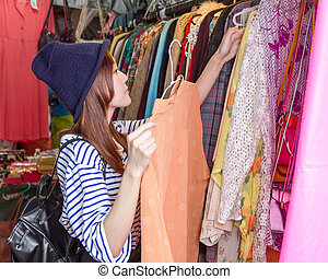 Asian woman looking at clothing