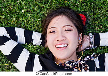 Asian woman lying on the grass in t